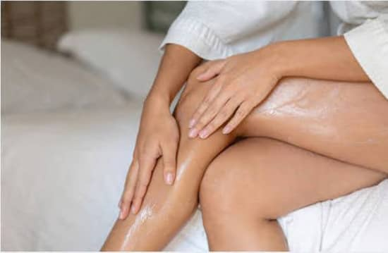 woman applying body shimmer lotion