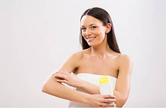 woman applying body shimmer to arms